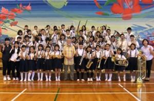 鈴木孝佳さん(中央)を囲んで記念撮影する子どもたち=16日、与論町砂美地来館(西村さん提供)