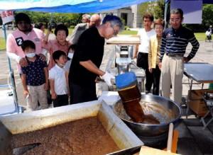 黒砂糖の製造工程を珍しそうに見入る市民ら(上)と、六調などでにぎわった「島唄の饗宴」=1日、鹿児島市山下町