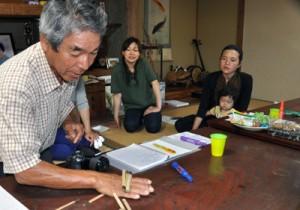 竹を使った手遊びを教える竹さん(左)=28日、与論町古里
