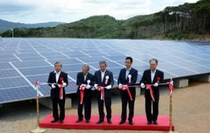 4千枚超の太陽光パネル前でテープカットを行った「開運発電所」の開所式=16日、宇検村湯湾の赤土山