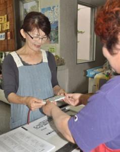 販売初日に商品券を買い求める町民=1日、龍郷町浦の島育ち館