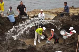 岩に海水をたたきつける汐干し体験をする児童ら=23日、和泊町国頭の海岸