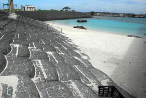 人工海浜の小野津海水浴場と、ウミガメの産卵環境保全へ設置されたふ化場=喜界町