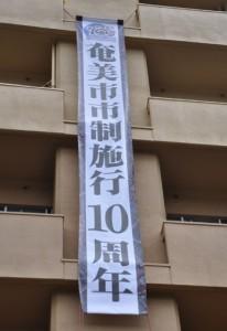奄美市の市制施行10周年を祝う懸垂幕=4日、奄美市役所