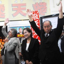 家族や支持者と共に万歳三唱し、初当選を喜ぶ鎌田氏(右)=14日午後9時45分、瀬戸内町古仁屋の選挙事務所