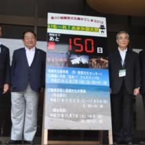 啓発用カントダウンボードを設置した実行委員会幹部ら=3日、奄美市役所