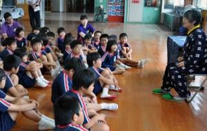 荒石さん(右)の語りを熱心に聞く子どもたち=8日、和泊町の内城小学校