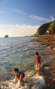 全国で最も暑い日に水遊びを楽しむ児童ら=9日、奄美市名瀬の大浜海浜公園