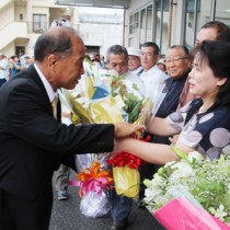 初登庁で職員から花束を受け取る鎌田愛人町長=25日、瀬戸内町役場