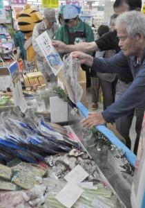 トカラ列島の特産品を品定めする買い物客ら=6日、奄美市名瀬