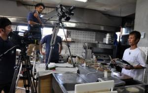 「お魚クッキング」の収録に臨む山下代表(右)=15日、和泊町伊延の飲食店
