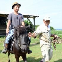 引き馬と呼ばれる乗馬体験。慣れれば1人で乗ることも可能=26日、奄美市笠利町