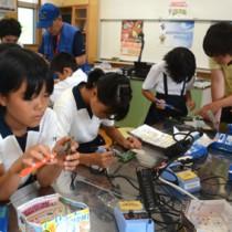 トランジスタラジオの組み立て体験などを通して電波の正しい利用ルールを学んだ電波教室=18日、龍郷町の大勝小学校