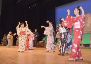 出演者らが六調を歌い踊って締めくくった「シマあすびの夕べ」=30日、奄美市名瀬の奄美文化センター
