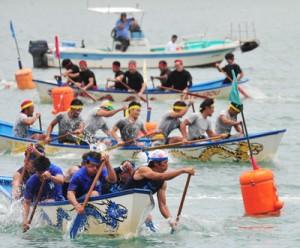 手に汗握るレースで観客を沸かせた龍郷ふるさと祭の舟こぎ競争=26日、龍郷町
