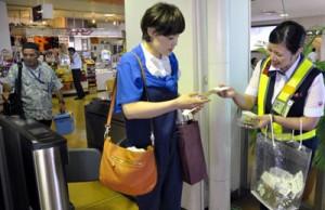 出発客に奄美の特産品を配布=1日、奄美空港