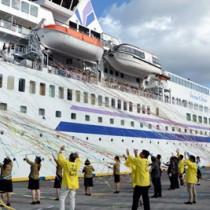 島唄や紙テープなど奄美ならではのスタイルで450人の乗船客を見送った=23日、奄美市名瀬