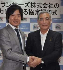 協定調印後に握手を交わす朝山市長(右)と秋好社長=1日、奄美市役所