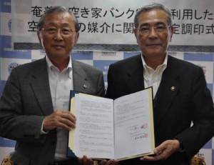 協定調印を交わした朝山市長(右)と本村会長=8日、奄美市役所
