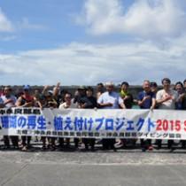 開会式で記念撮影するプロジェクト参加メンバー=18日、知名町の沖泊漁港