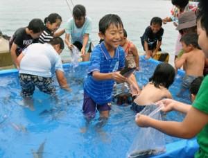 「グルクンのつかみ取り」で楽しそうに魚を追い掛ける子どもたち=19日、沖永良部島漁協