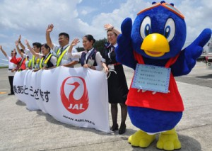 出発便を見送るJACキャラクター「ルリー」と職員=1日、奄美空港