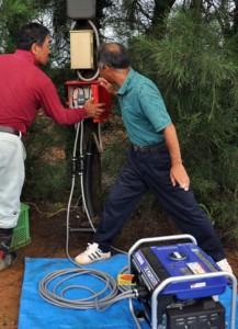 小型発電機によるLED電球点灯を試す関係者=24日、和泊町
