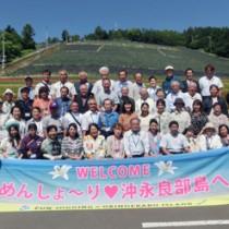 花畑の前で記念撮影する和泊町の訪問団=6日、北海道・中富良野町(和泊町役場提供)