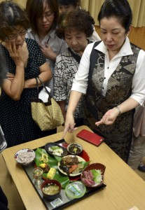 「奄美健康ランチ」を受講生に紹介する久留さん(右)=18日、県立奄美図書館