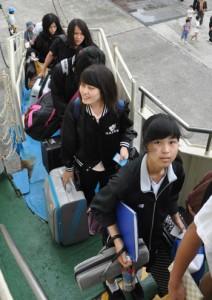 徳之島高校野球部の応援へ出発する生徒ら=21日、亀徳新港