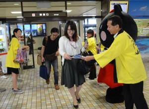到着客にガイドブックを手渡す奄美観光物産協会の会員ら=17日、奄美市