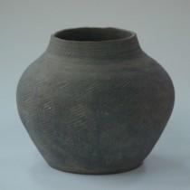 奄美市博物館に寄贈されたカムィヤキ壺形陶器と寄贈した吉村裕一さん(写真左、いずれも提供写真)