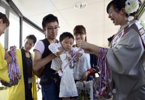 成田から着いて記念品を受け取る家族連れ=1日、奄美市笠利町の奄美空港