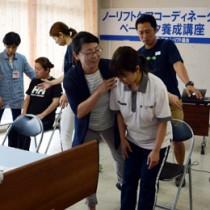 腕を使った起立介助法のこつを教える保田さん(中央)=2日、奄美市名瀬の生協会館
