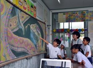 教室の黒板に描かれたアート作品を見つめる小湊小の児童たち=14日、奄美市の小湊小学校