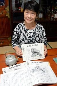 元明盛さんが戦後までを詳細にまとめた生涯日記を手にする長女の碩八重子さん=13日、奄美市名瀬
