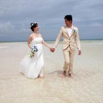 百合ヶ浜でロケーション撮影する千葉さん夫妻=4日、与論島(フォトスタジオ メデオ提供)