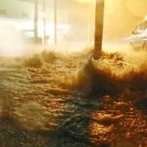 記録的な大雨で各地で道路が冠水。側溝から水が噴き出す県道=25日午後8時20分ごろ、徳之島町亀津