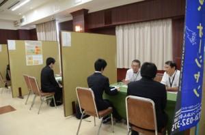 事業概要などを説明する企業ブースが並んだ会場=7日、奄美市