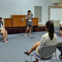 奄美からも9人の高校生が参加した「イングリッシュキャンプ」。中央はディベートに挑戦する沖永良部高校の新納優奈さん=11日、鹿児島市宮之浦町