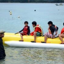 バナナボートなどマリンスポーツを満喫した七ヶ宿町と宇検村の児童たち=18日、宇検村タエン浜