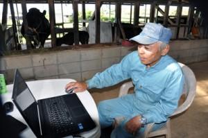 パソコンでネットワークカメラの状態を確認する上野さん=7月28日、与論町那間
