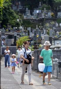 ちょうちんを手に先祖の霊を自宅へと導く人々=26日、奄美市名瀬の永田墓地