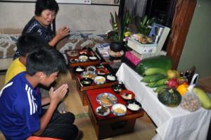 昔ながらの膳を先祖に供え、孫たちと手を合わせる東なつえさん(奥)=13日、知名町瀬利覚