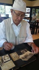 妹2人と映った写真を手に当時の記憶をたどる米田正英さん(上)と疎開船の船上で亡くなったことが記載されたフサ子さんの戸籍謄本
