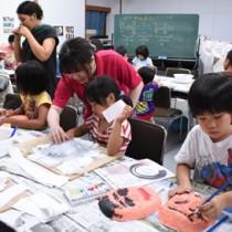 真剣な表情で仮面に色を塗る子どもたち=6日、瀬戸内町立図書館・郷土館