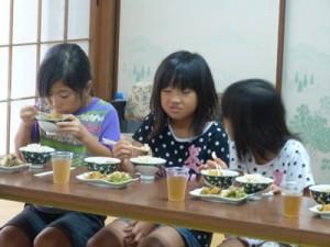 戦中戦後の食事を体験する児童ら=15日、喜界町中央公民館(提供写真)