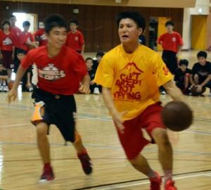 鮫島選手(右)とマンツーマンでボールを奪い合う中学生=17日、名瀬総合体育館