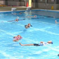 ペットボトル浮きに挑戦する参加者=22日、与論町B&G海洋センタープール