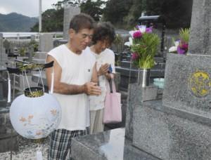 墓前で手を合わせ、先祖の霊を迎える夫婦=13日、奄美市名瀬大熊地区の墓地